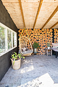 Hanging chair in rustic summerhouse with wooden wall