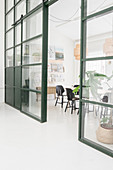 Sliding door in glass-and-steel wall leading into vintage-style conference room