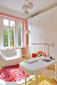 Weißer Designersessel, Schrank und Schreibtisch im Arbeitszimmer