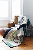 Quilt on rustic armchair with hessian cover