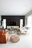 TV against black wall, white designer armchairs, coffee table and brown leather armchair in elegant living room