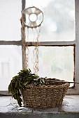 Korb mit Kräuter auf Fensterbank, Traumfänger am Fenster