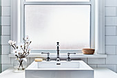 White washstand with countertop sink and spherical vase of magnolia flowers below window in bathroom