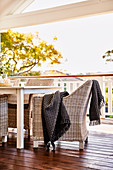Wicker armchairs around table on wooden terrace