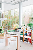 Home office with open bookcase and table in front of floor-to-ceiling glass