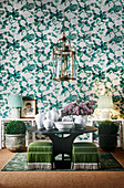 Green and white wallpaper with floral pattern, round table with white ceramics and lantern light