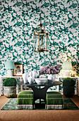 Grün-weiße Tapete mit Blumenmuster, runder Tisch mit weißer Keramik und Laternenleuchte