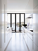 White designer kitchen with balcony door and sea view