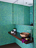 Mirror cabinet and vanity in the bathroom with mosaic tiles in green tones