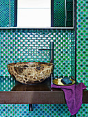 Wash basin in the bathroom with green mosaic tiles