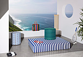 Mattress and pouf with colorful covers on terrace with sea view