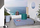Matratze und Sitzpouf mit bunten Bezügen auf Terrasse mit Meerblick