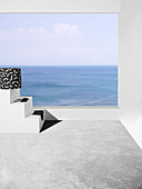 Pouf with black and white cover and bikini on terrace with sea view