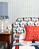 Bed with patterned headboard in front of stripe wallpaper, antique bedside table with table lamp and clock