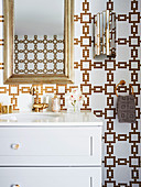 Gold frame mirror over white vanity in luxurious bathroom with gold and white mosaic tiles