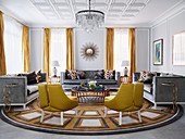 Gold-colored designer chairs and gray sofas with velvet upholstery around a marble table in a luxurious living room