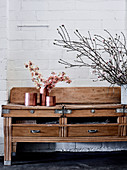 Old wooden table with drawers and vessels in rose gold with orchid flowers