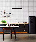 Black kitchen counter and black fridge in front of wallpaper with grid pattern, dining table and chair