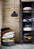 Stack of pillows next to black cupboard with home textiles