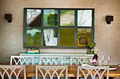 Esstisch mit Stühlen, dahinter Anrichte und Patchwork-Bild an tapezierter Wand