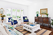 Living room with antique sideboard, blue upholstered armchairs and white coffee table