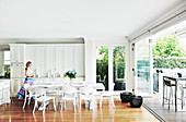 Woman walks through living kitchen with white furniture to the terrace
