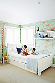 Children on the bed in the children's room with mint green wallpaper