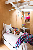 Bed under ceiling fan in girl's room with wooden paneling