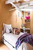 Bett unter Deckenventilator im Mädchenzimmer mit Holzverkleidung