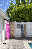 Pink surfboard on natural stone wall, next to white painted wooden fence