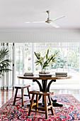 Runder Tisch mit passenden Holzhockern auf Teppich vor Terrassentür