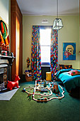 Wooden train on green carpet, bed, colorful curtain and fireplace in the children's room