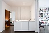 Fensterlose Küche mit weißen Einbauschränken und Schiebetür