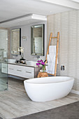 Free-standing oval bathtub and ladder towel rack in open-plan bathroom