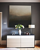 Painting with gradient of greys on grey wall above chest of drawers