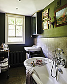 Vintage-style furnishings in dark bathroom with sash window