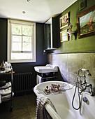 Nostalgische Einrichtung im dunklen Badezimmer mit Schiebefenster