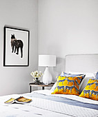 Cushions with zebra motif on double bed and side table with table lamp in bright bedroom