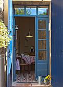 Blick durch geöffnete Terrassentür mit blau lackiertem Rahmen in Wohnküche