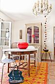 Runder Esstisch mit Klassikerstühlen auf orangefarbenem Teppich, im Hintergrund Anrichte