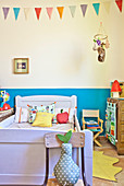 Colourful scatter cushions on wooden bed below bunting in child's bedroom