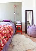 Bett mit lila Bettwäsche, roter Hocker mit Kissen und Glübirne mit rotem Kabel, lila Korb vor Standspiegel im Schlafzimmer