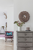 Grey chest of drawers with autumnal decorations and antique lilac armchair with blue scatter cushion in background