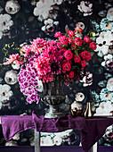 Opulenter Blumenstrauß in einer Amphore vor Blumentapete