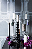 Various candle holders in front of a wallpaper with an architectural motif