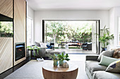 Modern living room in natural tones with a view of the garden