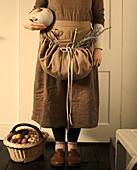 Frau in brauner Bekleidung mit Kürbis und Korb mit frisch geernteten Äpfeln