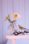 Christrose in Vase und Glasvogel auf Zweig als Weihnachtsdekoration