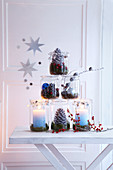 Festive pyramid of storage jars, pine cones and berries