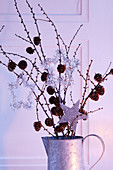 Christmas arrangement of branches of cones and silver star decorations